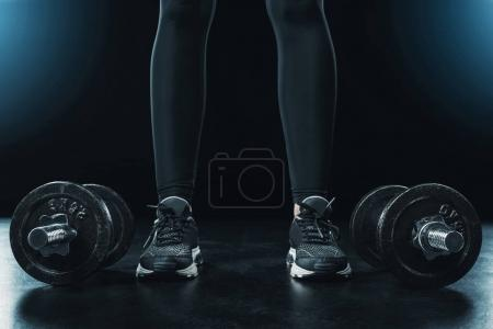 Photo for Low section of sportswoman standing near dumbbells isolated on black. - Royalty Free Image