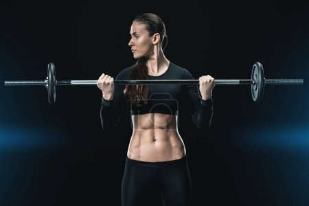 Photo for Young fitness woman training with barbell isolated on black. - Royalty Free Image