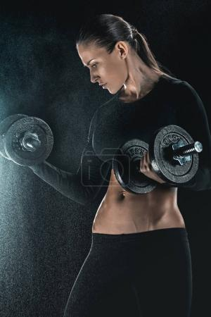 Photo for Young fitness woman training with dumbbells isolated on black. - Royalty Free Image