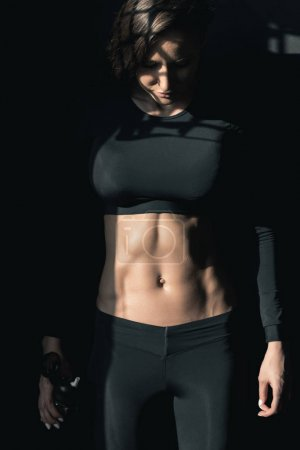 Photo pour Jeune femme de fitness en tenue de sport tenant bouteille de sport et regardant vers le bas - image libre de droit
