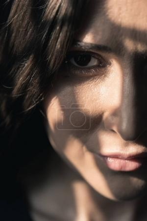 Photo pour Gros plan portrait demi-visage de belle jeune femme brune isolée sur noir - image libre de droit