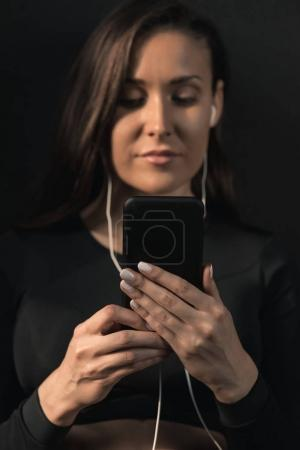 Photo for Attractive young brunette woman in earphones using smartphone - Royalty Free Image