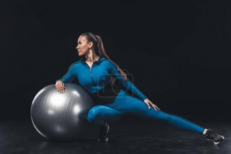 Photo for Athletic young woman in sportswear stretching with fitness ball - Royalty Free Image
