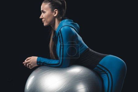 Photo pour Vue latérale de la jeune femme athlétique en vêtements de sport faisant de l'exercice avec balle de fitness - image libre de droit