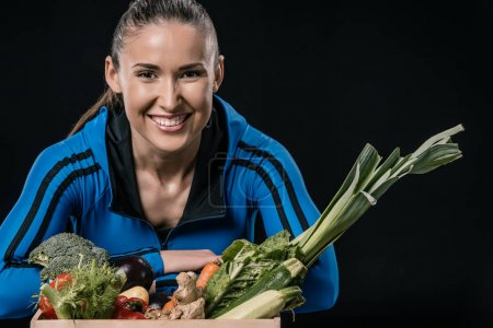 Photo for Young smiling sportswoman with fresh vegetables, healthy living concept - Royalty Free Image