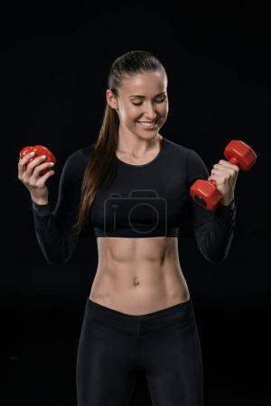 Sportswoman with pepper and dumbbell