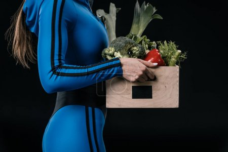Sportswoman with fresh vegetables