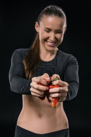 Photo for Smiling young fitness woman squeezing pepper in hands isolated on black - Royalty Free Image