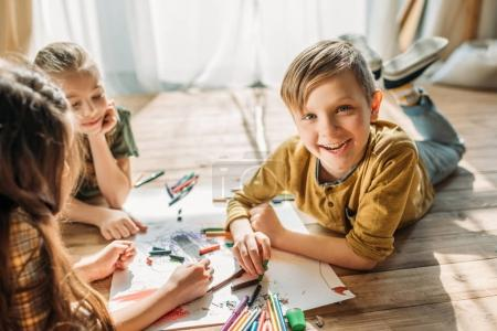 Photo for Cute kids drawing on paper with pencils while lying on floor - Royalty Free Image