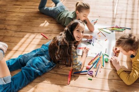 Photo pour Mignon enfants dessin sur papier avec des crayons tout en étant couché sur le sol - image libre de droit