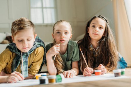 Photo for Cute kids painting on paper with while lying on floor at home - Royalty Free Image