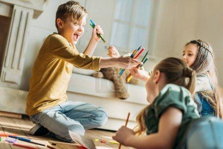 Photo pour Heureux enfants mignons dessin sur papier avec des crayons tout en étant assis sur le sol - image libre de droit