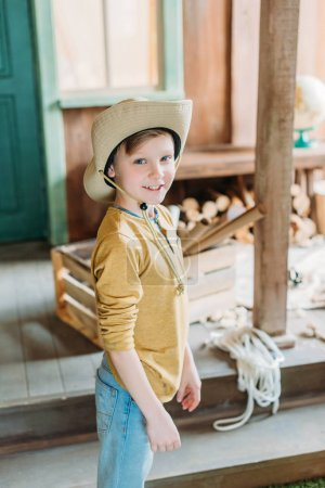 Photo for Smiling boy in hat standing on porch and looking at camera. cute kids concept - Royalty Free Image