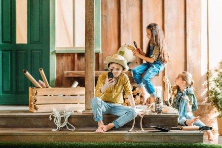 Photo pour Trois mignons petits enfants assis sur le porche avec différents articles de voyage - image libre de droit