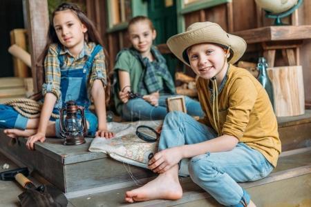 Photo pour Adorables petits enfants voyageurs assis avec carte sur le porche - image libre de droit