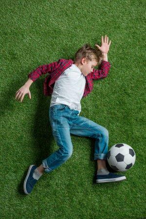 Photo pour Vue du dessus du garçon avec ballon de football couché sur l'herbe verte - image libre de droit
