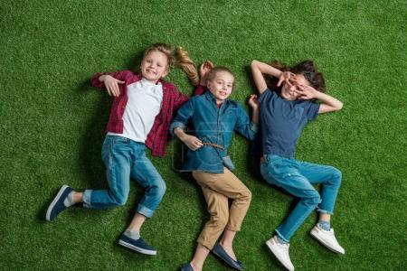 Photo pour Vue du dessus de trois adorables enfants couchés ensemble sur la pelouse verte - image libre de droit
