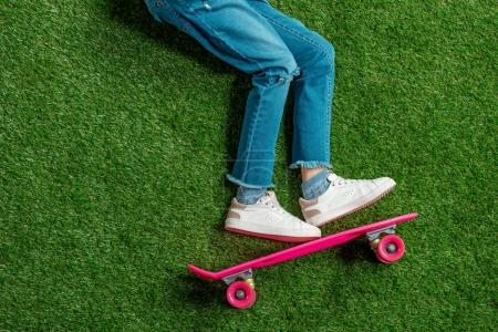 Girl with skateboard lying on grass