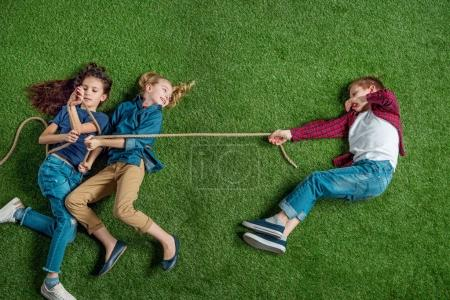 Photo for Top view of cute girls and boy lying on grass and playing tug of war - Royalty Free Image