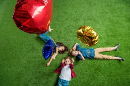 Photo pour Vue du dessus de trois mignons enfants allongés sur de l'herbe verte avec des ballons - image libre de droit