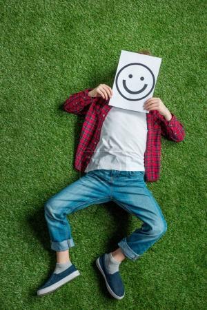 Photo pour Vue de dessus de l'enfant couché sur l'herbe et couvrant le visage avec l'image - image libre de droit