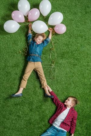 Boy holding girl with balloons