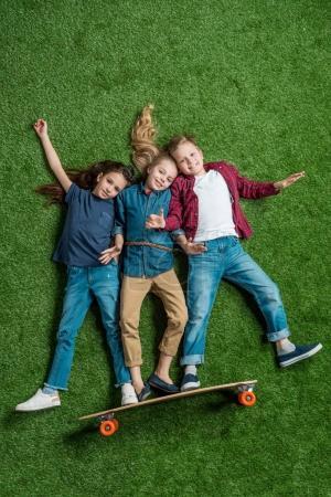 Photo pour Vue de dessus des enfants faisant semblant debout sur le skateboard sur l'herbe verte - image libre de droit
