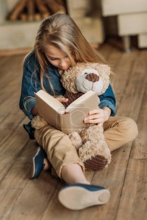 Photo pour Petite fille concentrée avec livre de lecture d'ours en peluche, concept d'éducation des enfants - image libre de droit