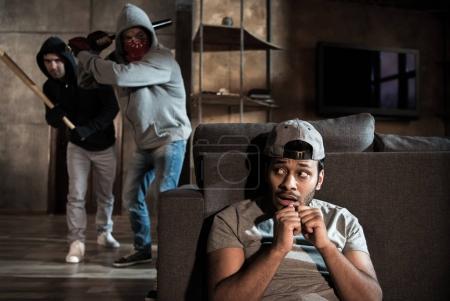 Foto de Hombre asustado escondiéndose detrás de sofá de ladrones, escena de robo de casa - Imagen libre de derechos