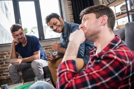 Foto de Tres sonrientes los hombres jugando a las cartas en la mesa de juego en el interior - Imagen libre de derechos