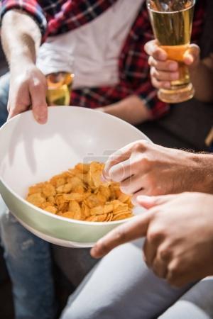 Friends eating crisps