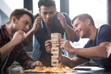 young people playing jenga game