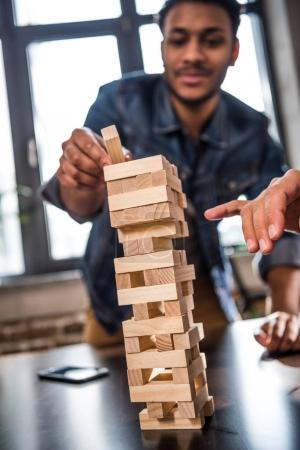 Photo for Happy friends playing jenga game, focus on foreground - Royalty Free Image