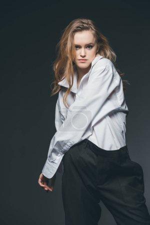 Photo pour Jeune femme adulte debout et posant sur fond noir, studio shot - image libre de droit