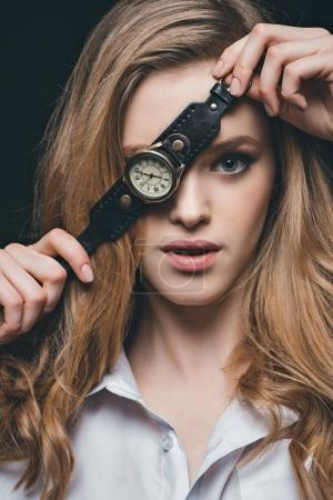 Girl hiding eye with vintage watch