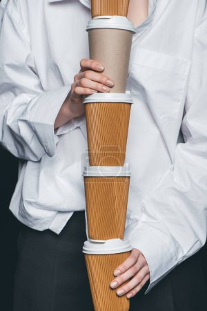 Woman holding pile of disposable coffee cups