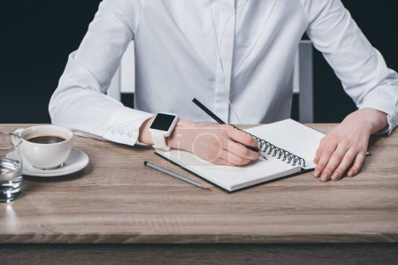 Photo for Cropped image of woman in white shirt and earphones sitting at table and making notes in notebook - Royalty Free Image
