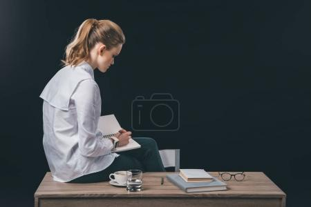 Woman sitting on table and making notes