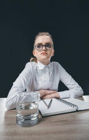woman in eyeglasses sitting at table