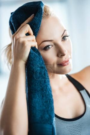 beatiful fitness woman with towel, resting after training