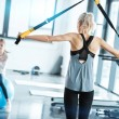 Blonde fitness woman training with trx fitness str...