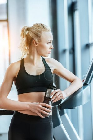 Young attractive woman resting after workout on treadmill