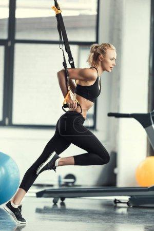 Photo pour Femme blonde fitness formation avec des sangles trx fitness - image libre de droit