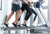 Family workout on treadmill, side view