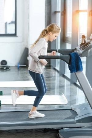 Blonde girl workout on treadmill, side view