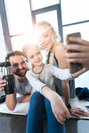 Girl taking self portrait with parents at fitness center