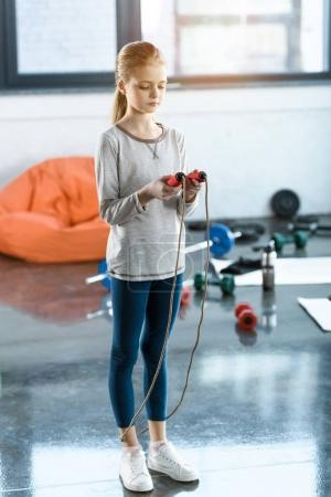 Young girl with skipping rope at fitness studio