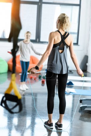 Young fitness people exercising with skipping ropes at sports center