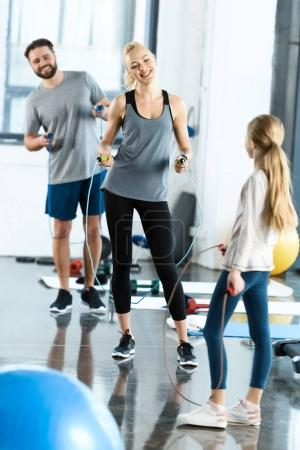 Young parents and daughter with skipping ropes at health club