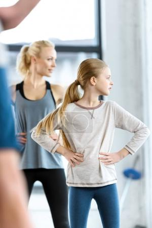 Young woman and cute girl exercising with coach at fitness studio